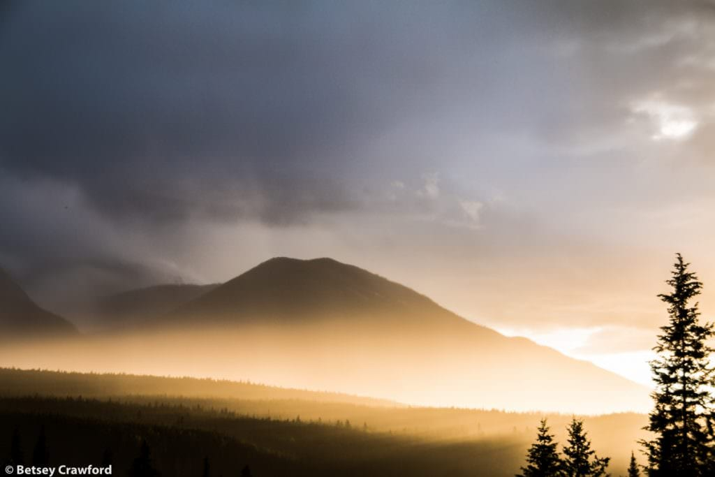 The sun emerges from under the clouds as it sets in Donald, British Columbia by Betsey Crawford